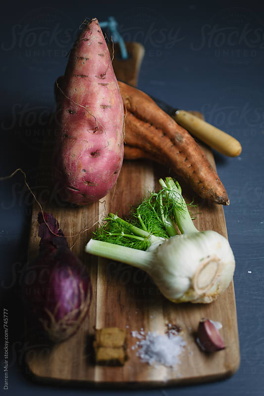 Ingredients for making roasted sweet potato and fennel soup on wooden board. by Darren Muir for Stocksy United