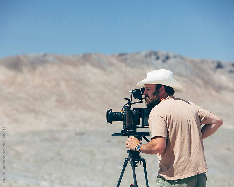 Filmmaker using digital cinema camera, composing shot, desert in distance by Paul Edmondson for Stocksy United