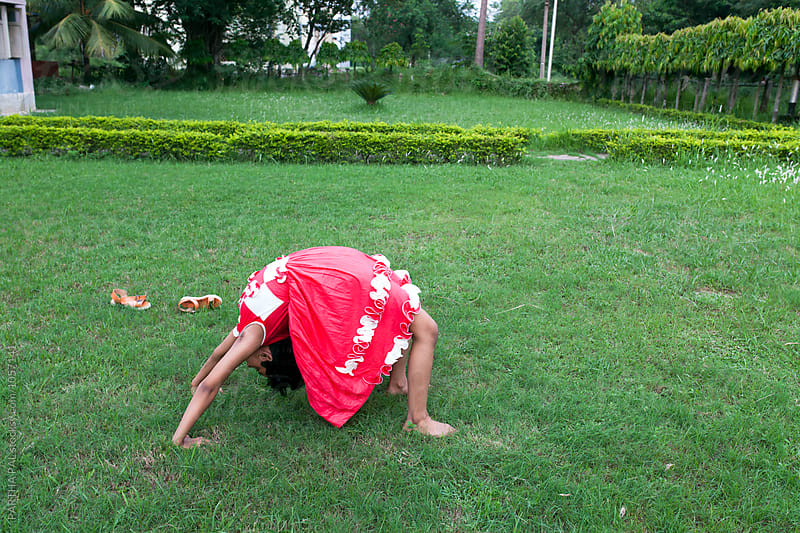 Teenage girl doing exercise in a green field by PARTHA PAL for Stocksy United