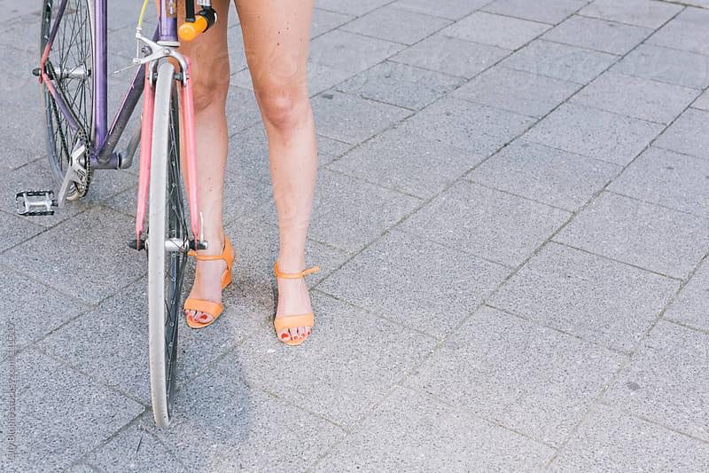 A fixed gear bike an the legs of a young woman on concrete by Lilly Bloom for Stocksy United
