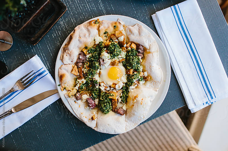 Margarita pizza with arugula and egg for breakfast by Kristen Curette Hines for Stocksy United
