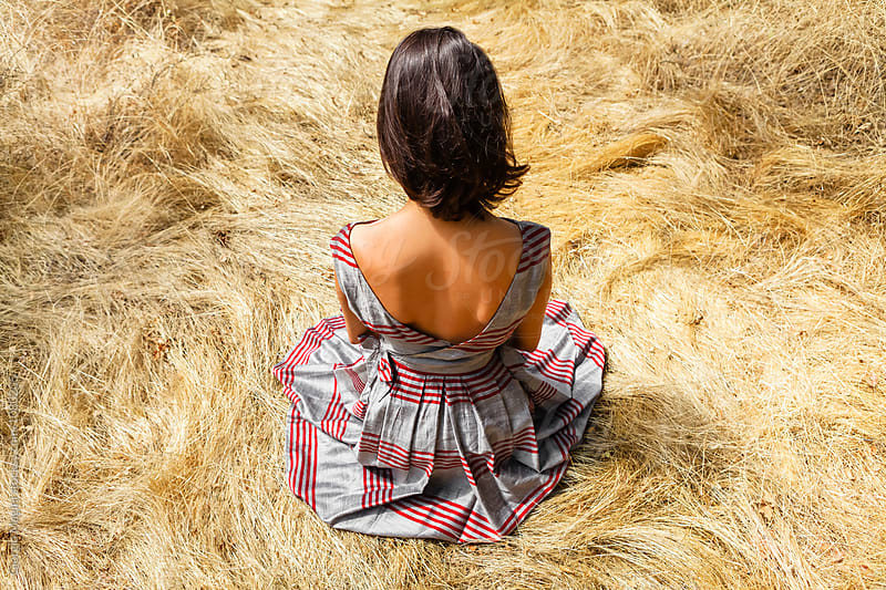 Young Woman Sitting on Hay with Vintage Dress by Giorgio Magini for Stocksy United
