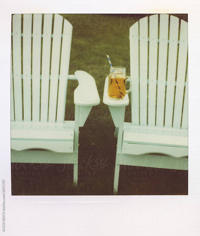 Two Adirondack Chairs And A Glass Of Iced Tea Photographed On Vintage Polaroid Film by ALICIA BOCK for Stocksy United