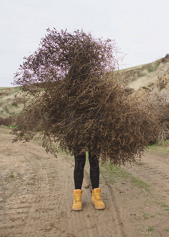 young woman holds gigantic tumbleweed by Tana Teel for Stocksy United