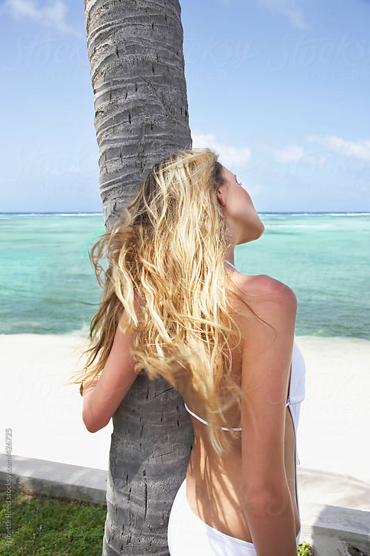 Beautiful woman relaxing on palm tree  by Trinette Reed for Stocksy United