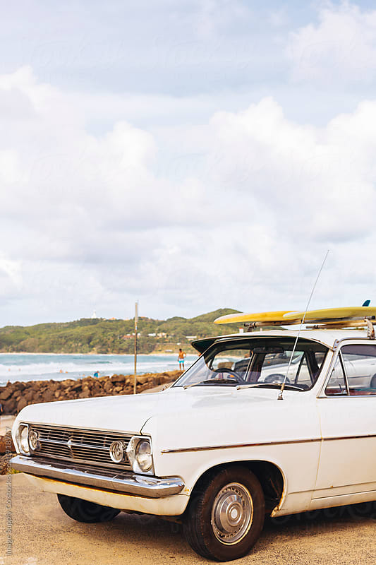 White vintage station wagon at rocky Australian beach. by Image Supply Co for Stocksy United
