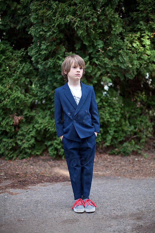 Boy in blue suit with t-shirt and skater shoes by Carleton Photography for Stocksy United