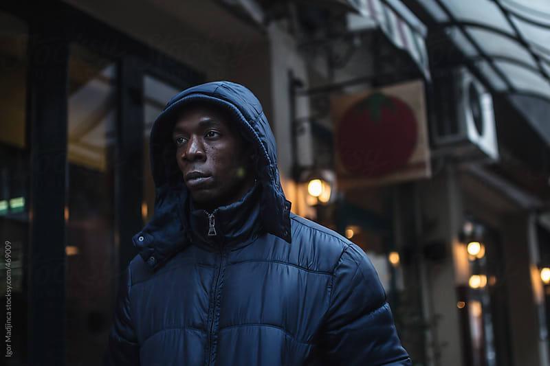 dark atmosphere,street portrait of black boy,Italian restaurant in the background by Igor Madjinca for Stocksy United