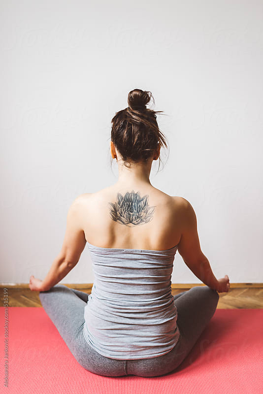 Back view of a tattooed woman meditating in the lotus position by Aleksandra Jankovic for Stocksy United