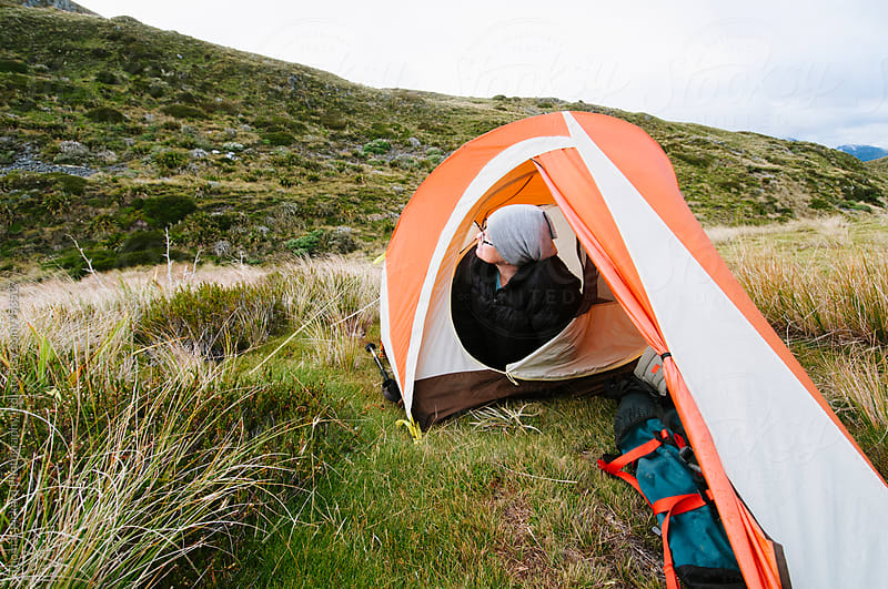 Woman trekker checking the weather from her tent, Kahurangi National Park, New Zealand. by Thomas Pickard for Stocksy United