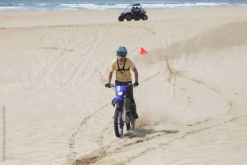 Young man riding a dirt bike on the sand dunes by Amy Covington for Stocksy United