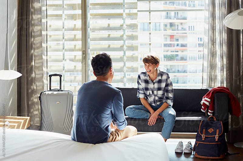 Cheerful Woman Talking With Man In Hotel Room by ALTO IMAGES for Stocksy United