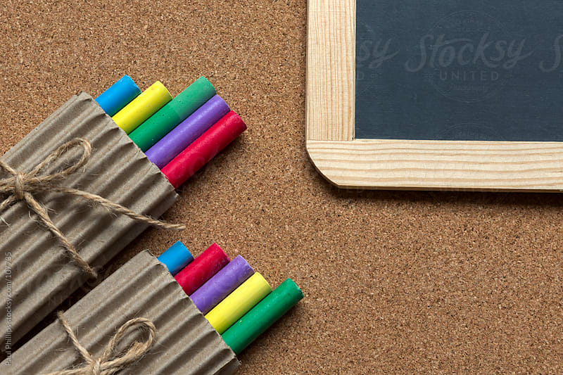Packaged crayons against a cork background with chalk board by Paul Phillips for Stocksy United