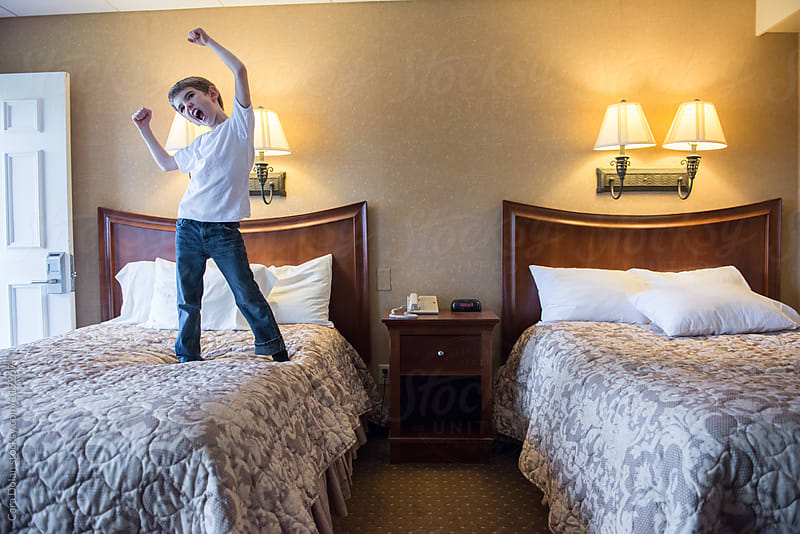 Boy goofs around in his hotel room while on vacation with his family by Cara Dolan for Stocksy United