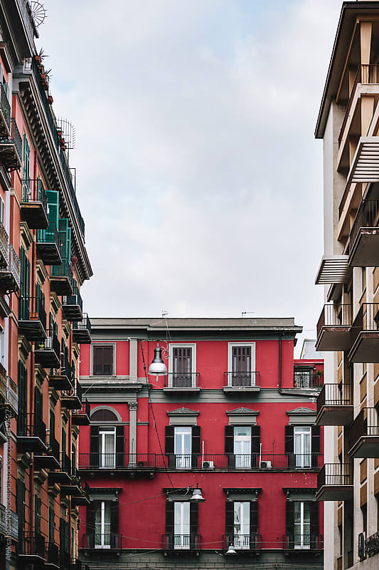 Building with red facade, surrounded by other two in Naples, Italy by Aleksandar Novoselski for Stocksy United