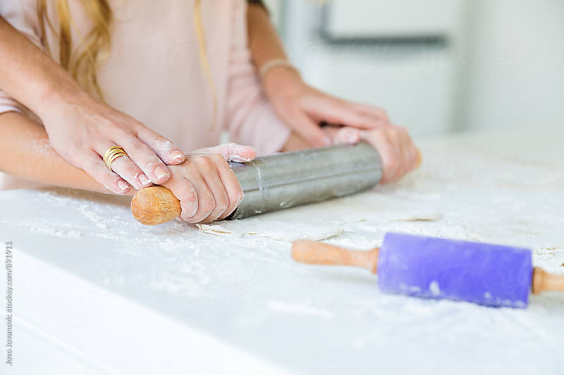 Mother and daughter hands kneading dough on the table by Jovo Jovanovic for Stocksy United