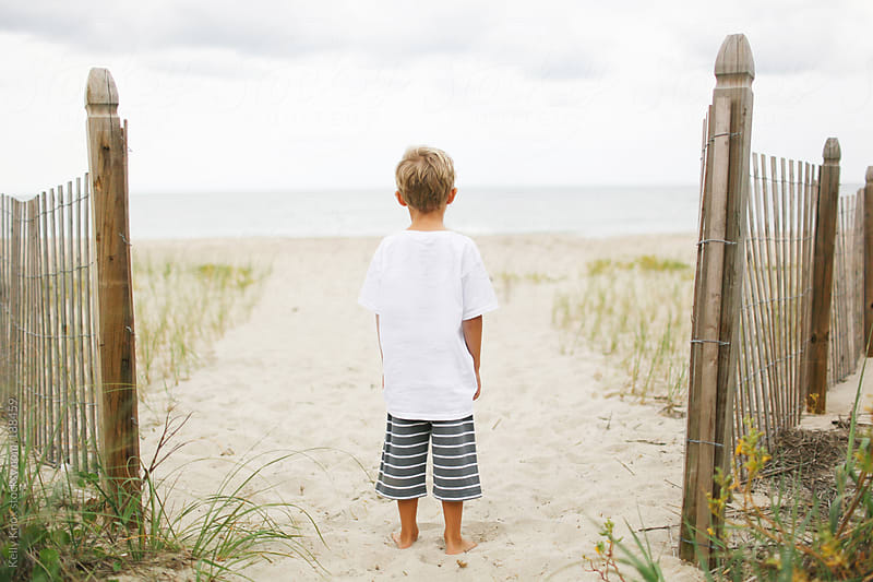 boy looking at the ocean by Kelly Knox for Stocksy United