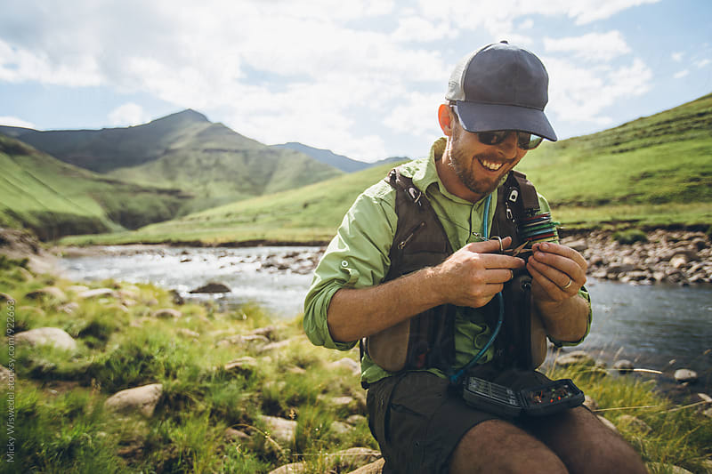 fly fisherman sitting near a river tying a fly by Micky Wiswedel for Stocksy United