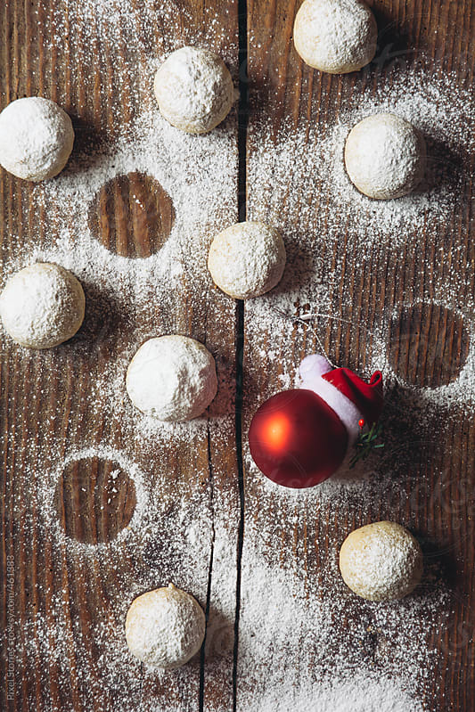 Russian tea balls on table with red Christmas bauble by Pixel Stories for Stocksy United