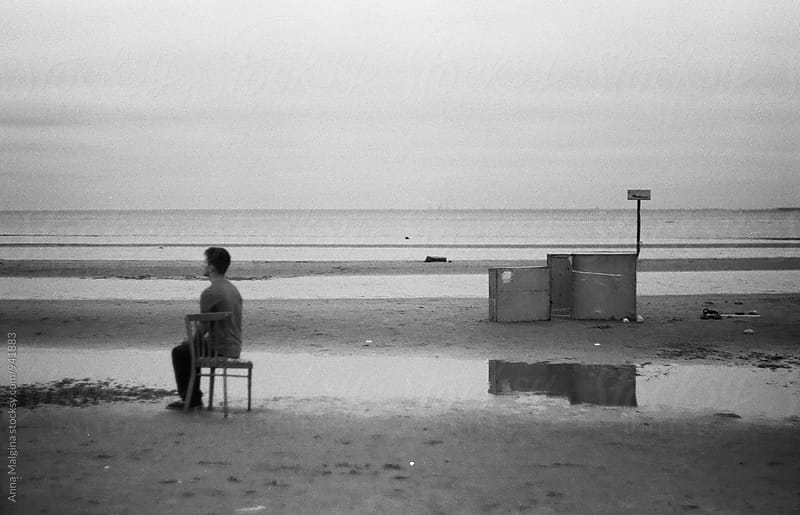 A black and white film portrait of young beautiful man seating on the beach by Anna Malgina for Stocksy United