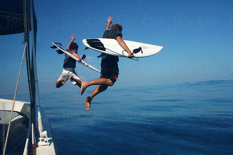Two surfers jump with their surfboards out of a boat by Denni Van Huis for Stocksy United