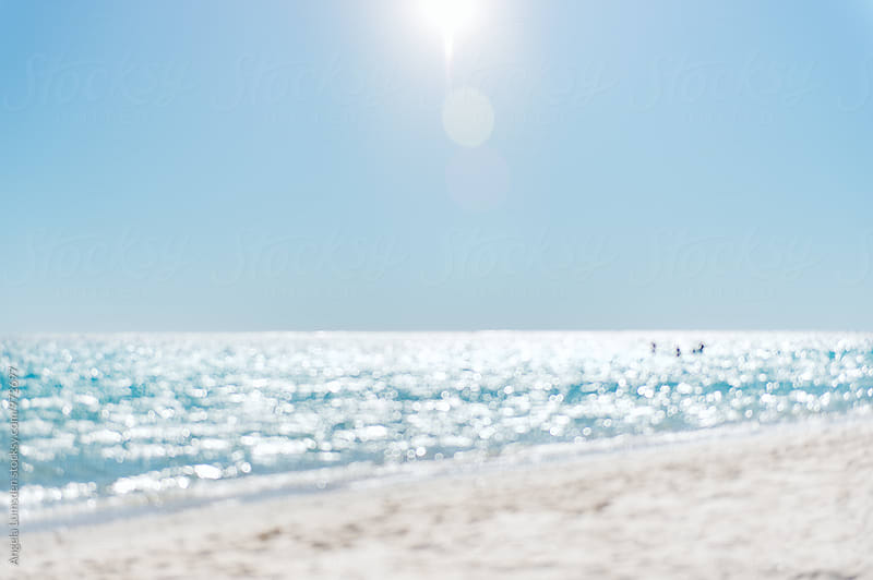 Blurred image of sunlight sparkling on the water at the beach by Angela Lumsden for Stocksy United