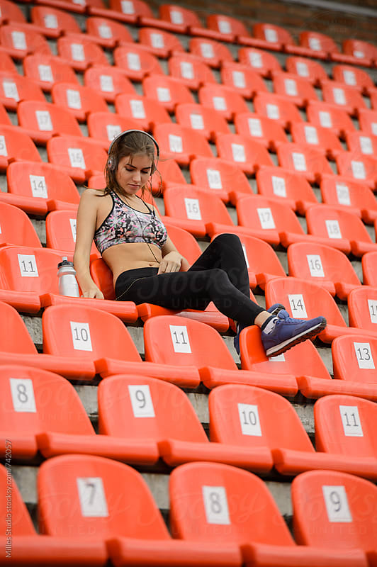 Woman sitting on stand of a stadium by Milles Studio for Stocksy United