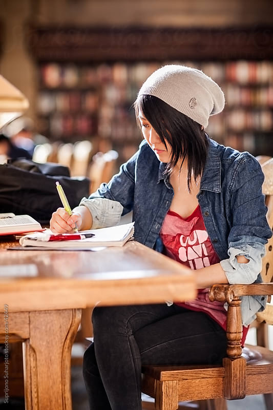 Asian college student studying in the library by Suprijono Suharjoto for Stocksy United