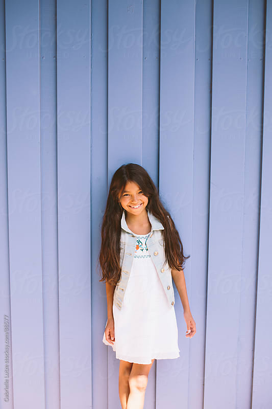 Young Girl in front of Blue Building by Gabrielle Lutze for Stocksy United