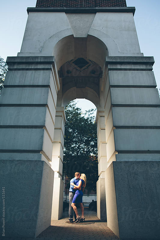 young couple kisses under archway by Brian Powell for Stocksy United
