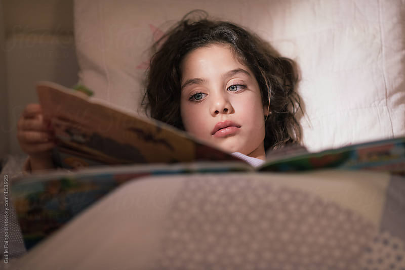 Cute girl reading a book in bed. by Guille Faingold for Stocksy United