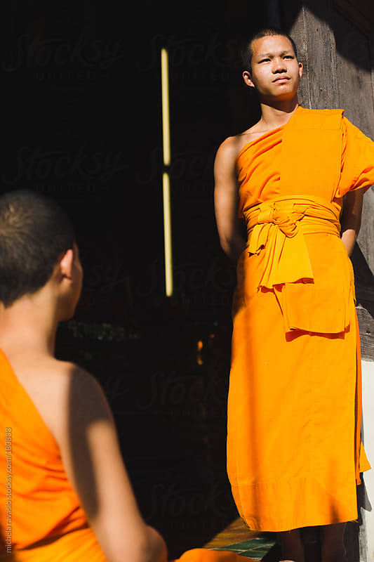 Young Buddhist monks at the temple entrance by michela ravasio for Stocksy United