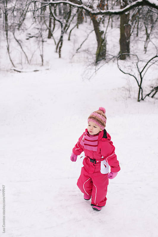 Little girl walking in snow enjoying time spent outdoors. by Lea Csontos for Stocksy United