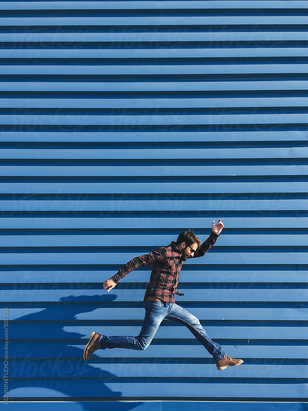 Young bearded man jumping in front a big blue factory door. by BONNINSTUDIO for Stocksy United