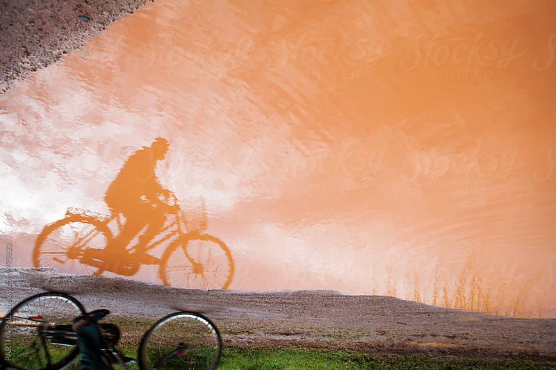 Shadow of a cyclist on rain clogged water by PARTHA PAL for Stocksy United