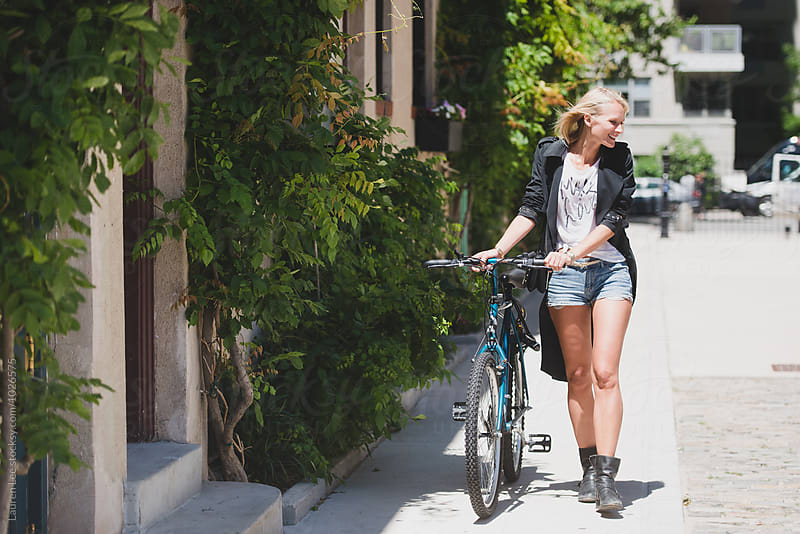 Young woman walking with bike in the city by Lauren Naefe for Stocksy United