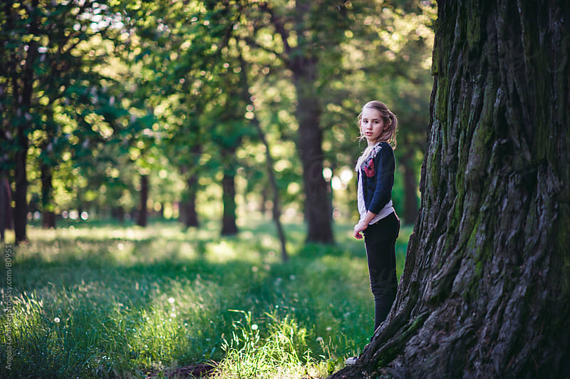 Girl standing beside a large tree in a park by Angela Lumsden for Stocksy United