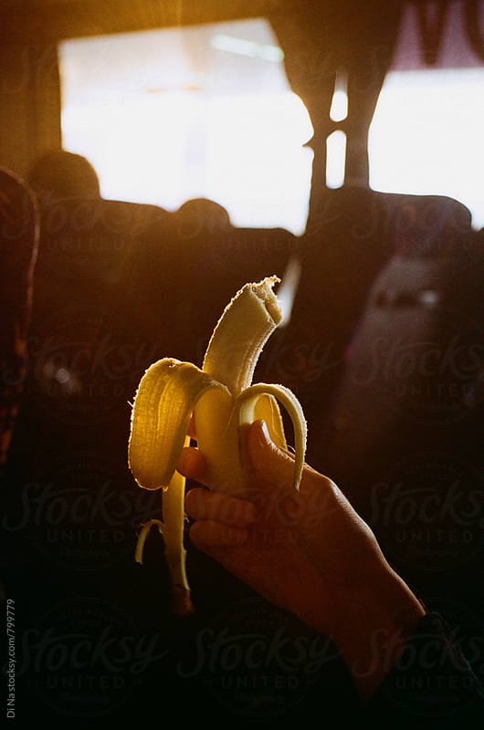 Man holding banana in the bus by Dina Lun for Stocksy United