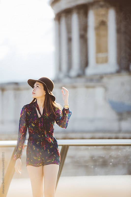Brunette girl wearing a hat walking towards camera on a city rooftop by Maresa Smith for Stocksy United