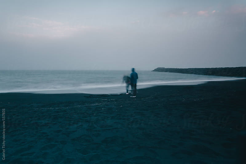 Black volcanic sand beach with two blurred people by Gabriel Tichy for Stocksy United