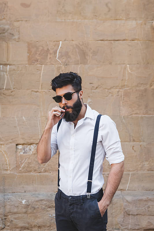 Serious Young Mobster Smoking a Cigar Outdoors by Giorgio Magini for Stocksy United
