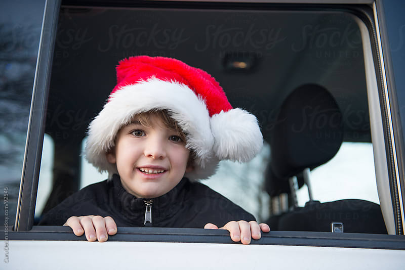 Cute boy wearing Santa Claus hat peeks out the window of the car by Cara Dolan for Stocksy United