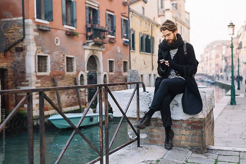 Young man using a smartphone outdoor. by Alberto Bogo for Stocksy United