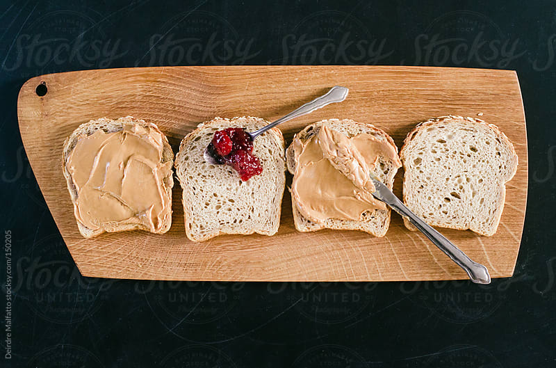 preparing peanut butter and jelly sandwiches by Deirdre Malfatto for Stocksy United