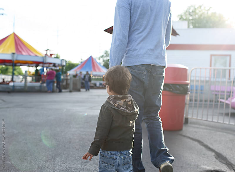 father and son walk at amusement park by Maria Manco for Stocksy United