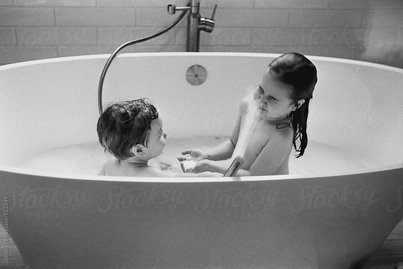 Young brother spraying his older sister with water in a bathtub by Jakob for Stocksy United