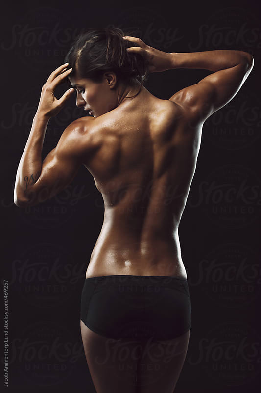 Portrait of fitness woman in studio by Jacob Ammentorp Lund for Stocksy United