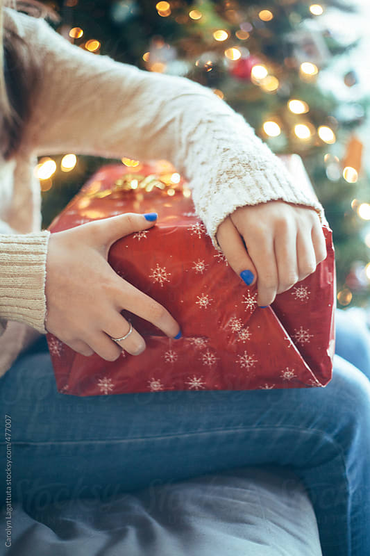 Teenage girl opening a Christmas present by Carolyn Lagattuta for Stocksy United