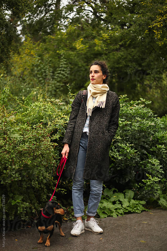 Woman with a dog in a park by Marija Kovac for Stocksy United