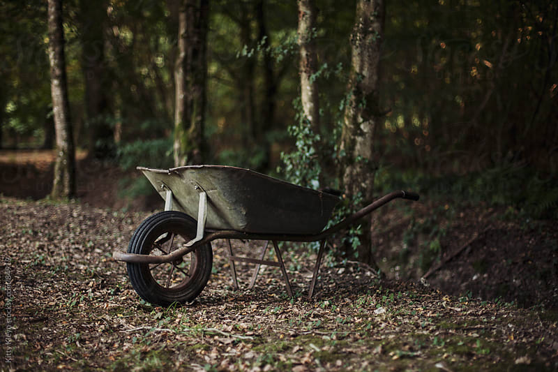 Wheelbarrow in the woods by Kitty Kleyn for Stocksy United